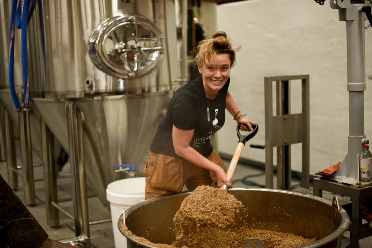 Anna får det tunga jobbet att tömma drav från första koket på Fermenterarnas nya bryggerilokaler.